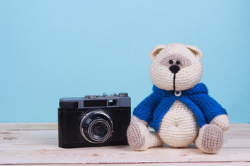 Teddy bear with old camera on blue background
