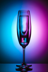 Champagne glass on color background
