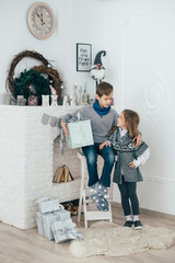 A boy is a schoolboy sitting with a sister near a fireplace