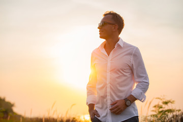 Handsome man in white shirt standing in sunset