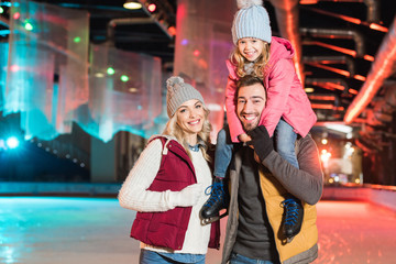 happy young family smiling at camera while spending time together on rink