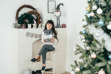 A girl sits at the fireplace and holds a box with a gift in her hands