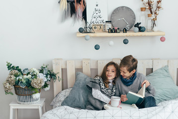 Brother and sister read an interesting book sitting in bed