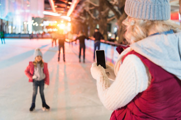 young woman with smartphone photographing cute little daughter on skating rink