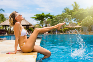 Cheerful woman having fun by the pool