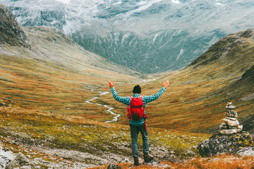 Man happy raised hands with backpack exploring mountains Travel heathy lifestyle concept active weekend summer vacations wild trek in Scandinavia