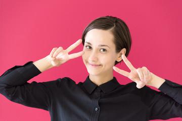 笑顔でピースするロシア人女性(赤・ピンク背景)