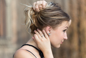 Side view of girl holding her hair in arms to show her earrings