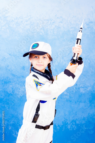 Young child girl female playing in astronaut with rocket toy in white astronaut costume and dreaming  sc 1 st  Fotolia.com & Young child girl female playing in astronaut with rocket toy in ...