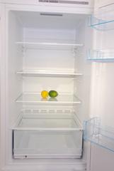 Citrus in open empty refrigerator.