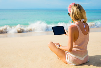 Hipster girl using tablet on the beach