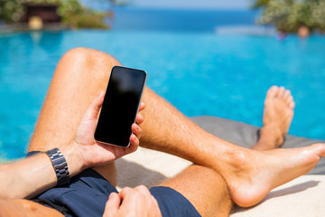 Man with mobile phone by the pool