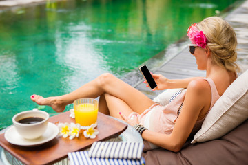 Hipster girl using mobile phone while relaxing by the pool on vacation