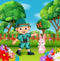 adventure cute boy with rabbit in a flower garden