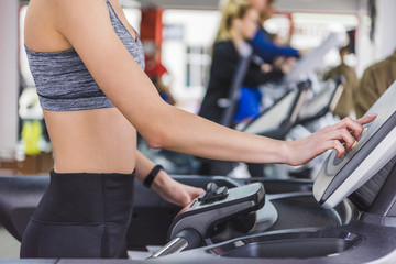 cropped shot of woman running on treadmill at gym