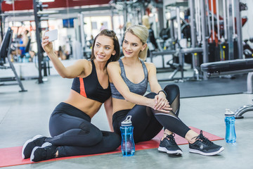 young sportive women taking selfie at gym