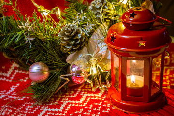 Christmas decoration with candle and garland lights on red rustic background
