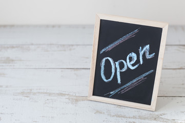 """Background with sign """"open"""" written on blackboard. Chalk lettering. Small business concept"""