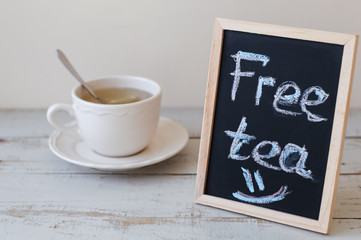 """Blackboard with handwritten chalk text """"Free tea"""" and a cup og green tea with lemon on wooden table. Hot beverage"""