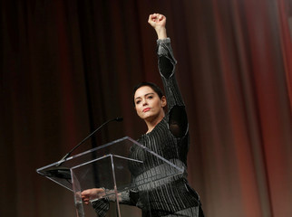 Actor McGowan raises her fist after addressing the audience during Women's Convention in Detroit