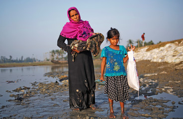 Mobaras Kharun, 40, carrying her newborn baby, and her daughter Shufaida Begum, 6, pose for a picture as they stand in the mud after crossing the Bangladesh-Myanmar border, at a port in Teknaf