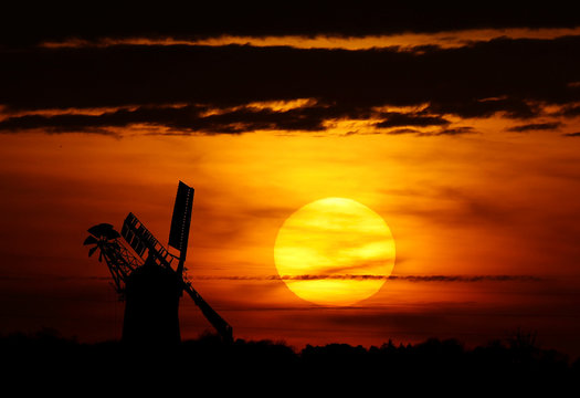 The sun sets behind a windmill belonging to Miller Nigel Moon in Whissendine