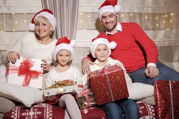 Fototapeta Rodzina na kanapie z prezentami podczas Świąt Bożego Narodzenia obraz