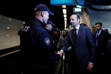 French Prime Minister Edouard Philippe shakes hands with a policeman during a visit in a metro station in Paris
