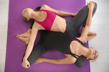 Two young women practicing yoga indoors