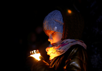 """Girl holds a candle during a """"Night of the executed poets"""" event at a mass grave in Kuropaty on the outskirts of Minsk"""
