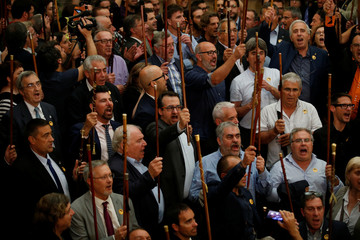 Mayors from pro indpendence towns raise ther scepters during a ceremony inside the Catalan regional Parliament after the parliament voted to declare independence from Spain in Barcelona