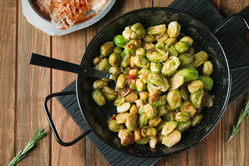 Frying pan with roasted Brussel sprouts and bacon on wooden table