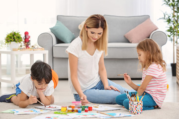 Mother with children painting while sitting on floor indoors