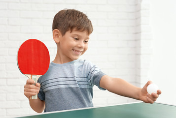 Cute little boy playing table tennis indoors