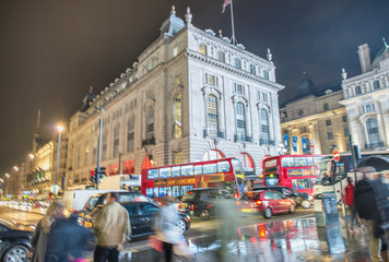 LONDON - OCTOBER 2013: Tourists walk in Piccadilly Circus, long exposure view. London attracts 30 million visitors annually