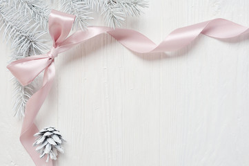 Mockup Christmas tree cone and pink ribbon bow, flatlay on a white wooden background, with place for your text