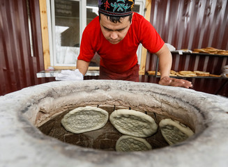 A worker looks at baking bread inside a tandoor clay oven in a bakery in a village of Guldala, outside Almaty