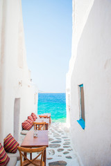 Benches with pillows in a typical greek outdoor cafe in Mykonos with amazing sea view on Cyclades...