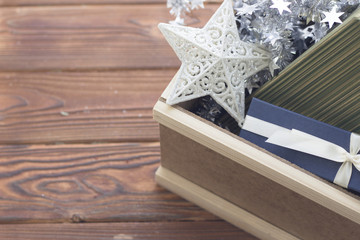 An edge of a wooden box filled with a white patterned star, silver garland, a green striped box and a blue gift box with a white satin ribbon. Rustic wooden background.
