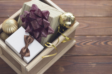 New year surprise in a wooden box. A white gift box with a brown satin bow, an olive green striped box with a purple bow and golden balls in a wooden drawer. Rustic wooden background.