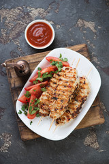 Lula kebabs with chicken meat, fresh vegetables and sauce on a rustic wooden serving board, flat-lay on a brown stone background