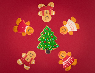 Christmas cookies of different shapes and sizes with a festive decor on a red background. Holiday Poster concept.  Empty place for a postural inscription
