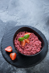 Risotto with strawberries in a bowl on a stone slate tray, vertical shot with copy space over gray concrete background