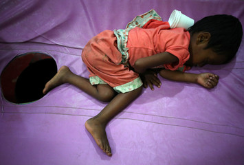 A Rohingya refugee girl suffering from severe diarrhoea lies on a bed in a diarrhoea treatment centre in Kutupalong refugee camp near Cox's Bazar