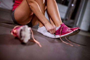 Close up of young fitness girl sitting on the gym floor and putting on her pink sneakers.
