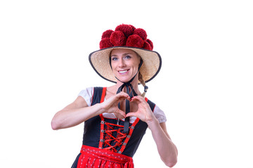 Woman wearing Black Forest dress showing heart sign