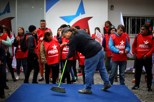 A man cleans the podium where Chilean conservative presidential candidate Sebastian Pinera will give a speech at a campaign rally in Santiago