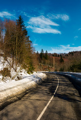 turnaround on the mountain road in winter. forested hills with snow on roadside under the clear blue sky