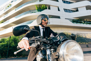 Portrait of mature businessman outdoors, sitting on motorcycle, wearing motorcycle helmet
