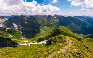 path along the mountain ridge with snow on hills. Gorgeous summer scenery in Fagaras mountains of Romania